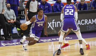 Sacramento Kings guard Buddy Hield (24) drives to the basket as teammate forward Richaun Holmes (22) assists during the first half of an NBA basketball game, Tuesday, Dec. 29, 2020 in Sacramento, Calif. (AP Photo/Hector Amezcua)