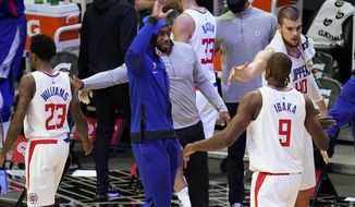 Los Angeles Clippers forward Kawhi Leonard, center, high-fives forward Serge Ibaka (9) during a timeout in the second quarter of the team's NBA basketball game against the Minnesota Timberwolves on Tuesday, Dec. 29, 2020, in Los Angeles. Leonard did not play due to injury. (AP Photo/Ashley Landis)