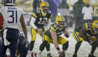 Green Bay Packers' Corey Linsley snaps the ball to Aaron Rodgers during the first half of an NFL football game against the Tennessee Titans Sunday, Dec. 27, 2020, in Green Bay, Wis. (AP Photo/Mike Roemer)