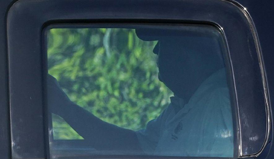 President Donald Trump rides in a motorcade vehicle as he departs his Mar-a-Lago resort, Wednesday, Dec. 30, 2020, in Palm Beach, Fla. Trump is en route to Trump International Golf Club in West Palm Beach, Fla. (AP Photo/Patrick Semansky)