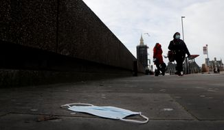 A mask on the pavement near the entrance of a hospital on Westminster Bridge in London, Wednesday, Dec. 30, 2020. Reports say that pressure on the NHS is rising and it is absolutely critical that people follow the rules and do everything they can to stop the spread, especially of the new variant of this virus that transmits so much faster.UK Health Secretary Matt Hancock said on Wednesday the Oxford-AstraZeneca drug approval will accelerate Britain's coronavirus vaccination programme.(AP Photo/Frank Augstein)
