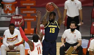 Michigan guard Chaundee Brown (15) shoots next to Maryland guard Darryl Morsell (11) during the first half of an NCAA college basketball game Thursday, Dec. 31, 2020, in College Park, Md. (AP Photo/Nick Wass) **FILE**