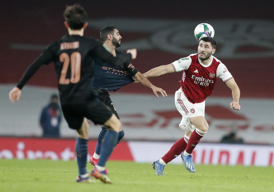 Arsenal's Sead Kolasinac, right, battles for the ball with Manchester City's Riyad Mahrez during the English League Cup quarterfinal soccer match between Arsenal and Manchester City at Emirates Stadium, London, Tuesday, Dec. 22, 2020. (AP Photo/Frank Augstein)