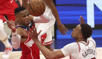 Washington Wizards' Russell Westbrook passes the ball around Chicago Bulls' Daniel Gafford, right, during the first half of an NBA basketball game Thursday, Dec. 31, 2020, in Washington. (Rob Carr/Pool Photo via AP)