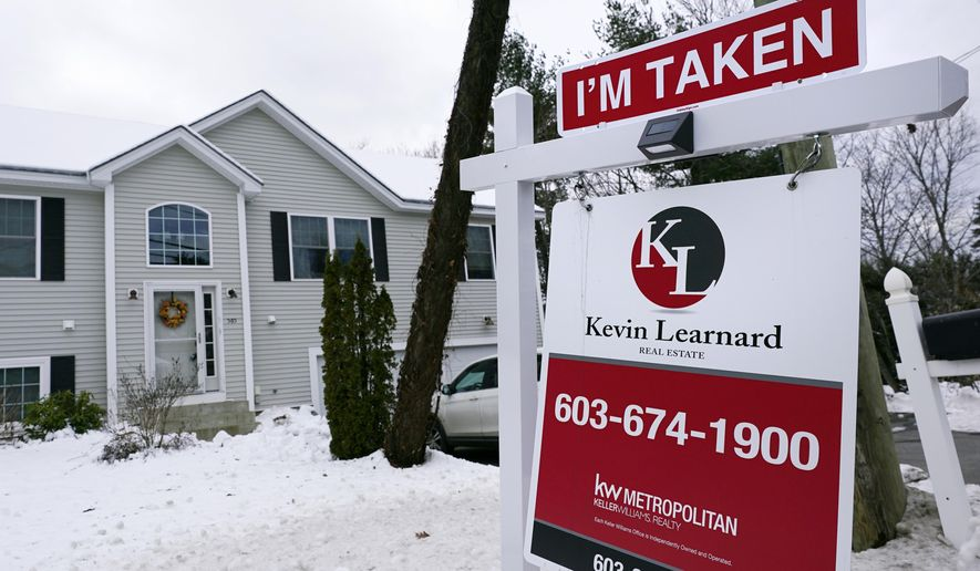 "An ""I'm Taken"" placard rests on a real estate for sale sign outside a home, Thursday, Dec. 10, 2020, in Manchester, N.H. U.S. long-term mortgage rates declined this week to record low levels for the 15th time this year against the backdrop of an economy ravaged by the pandemic. Mortgage finance giant Freddie Mac said Thursday, Dec. 17, 2020, that the average rate on the 30-year fixed-rate home loan fell to 2.67% from 2.71% last week. A year ago, the benchmark rate stood at 3.73%. (AP Photo/Charles Krupa)"