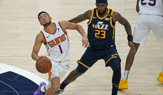 Phoenix Suns guard Devin Booker (1) drives around Utah Jazz forward Royce O'Neale (23) during the second half of an NBA basketball game Thursday, Dec. 31, 2020, in Salt Lake City. (AP Photo/Rick Bowmer)