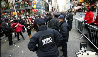 FILE - In this Dec. 31, 2014, file photo, New York Police Department counterterrorism officers, foreground, armed with an explosives detection device, far right, watch as other police officers inspect revelers entering a cordoned off area in Times Square in New York, on New Years Eve. Although New York City police have turned to familiar tactics ahead of the iconic Thursday, Dec. 31, 2020, ball drop, the department's playbook this year includes an unusual mandate: preventing crowds from gathering in Times Square. (AP Photo/Kathy Willens, File)