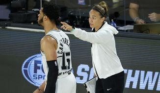 San Antonio Spurs assistant coach Becky Hammon talks with Quinndary Weatherspoon (15) during the second half of an NBA basketball game against the Utah Jazz in Lake Buena Vista, Fla., in this Friday, Aug. 7, 2020, file photo. Becky Hammon became the first woman to direct a team in NBA history, taking over the San Antonio Spurs on Wednesday night, Dec. 30, 2020, against the Los Angeles Lakers following Gregg Popovich's ejection in the first half.(Kevin C. Cox/Pool Photo via AP, File) ** FILE**