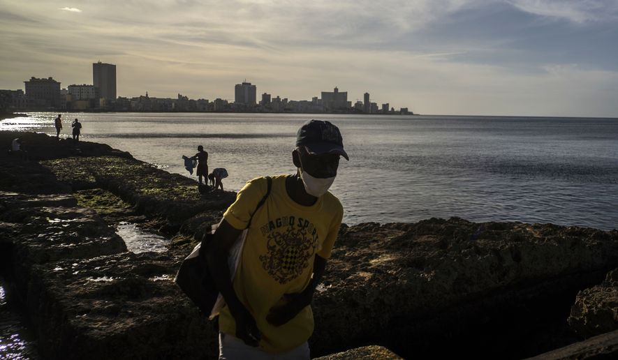 A man wearing a mask as a precaution against the spread of the new coronavirus walks next to people taking a sunbath at sunset on the Malecon in Havana, Cuba, Friday, Jan 1, 2021. (AP Photo/Ramon Espinosa)