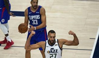 Utah Jazz center Rudy Gobert (27) flexes his muscles after scoring against Los Angeles Clippers' Nicolas Batum (33) during the second half of an NBA basketball game Friday, Jan. 1, 2021, in Salt Lake City. (AP Photo/Rick Bowmer)