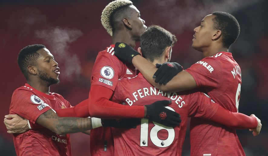 Manchester United's Bruno Fernandes, (18), celebrates with teammates after scoring his sides 2nd goal of the game from the penalty spot during the English Premier League soccer match between Manchester United and Aston Villa at Old Trafford in Manchester, England, Friday, Jan. 1, 2021. (Carl Recine/ Pool via AP)