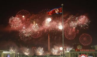 In this photo provided by the North Korean government, fireworks illuminate the night sky, marking the New Year, as crowds of people look on, at Kim Il Sung Square in Pyongyang, North Korea, early Friday, Jan. 1, 2021. (Korean Central News Agency/Korea News Service via AP)