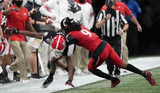 Georgia wide receiver George Pickens (1) is hit by Cincinnati cornerback Arquon Bush (9) during the second half of the Peach Bowl NCAA college football game, Friday, Jan. 1, 2021, in Atlanta. (AP Photo/Brynn Anderson)