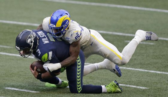 Seattle Seahawks quarterback Russell Wilson (3) is sacked by Los Angeles Rams outside linebacker Leonard Floyd (54) during the first half of an NFL football game, Sunday, Dec. 27, 2020, in Seattle. (AP Photo/Scott Eklund)