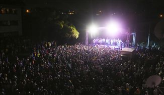 Thousands of people attend a music concert to celebrate New Year's in the Mbare suburb of Harare, Zimbabwe, early Friday, Jan 1, 2021. Despite a government ban on music concerts and public gatherings due to a surge in COVID-19 infections and the new and more contagious variants of the disease, thousands of people gathered in one of the country's poorest neighborhoods to celebrate the new year. (AP Photo/Tsvangirayi Mukwazhi)