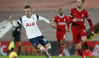 Tottenham's Giovani Lo Celso, left, takes the ball past Liverpool's Jordan Henderson during their English Premier League soccer match between Liverpool and Tottenham Hotspur at Anfield in Liverpool, England, Wednesday, Dec., 16, 2020. (Clive Brunskill/ Pool via AP)