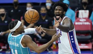 Philadelphia 76ers' Joel Embiid, right, and Charlotte Hornets' Devonte' Graham battle for the ball during the first half of an NBA basketball game, Saturday, Jan. 2, 2021, in Philadelphia. (AP Photo/Matt Slocum)
