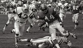 FILE - In this Sept.1969 file photo, Denver Broncos' Floyd Little avoids the tackle of New York Jets' Steve O'Neal (20) during a football game in Denver.  Little, the Hall of Fame running back who starred at Syracuse and for the Denver Broncos, has died.  The Pro Football Hall of Fame said he died Friday, Jan. 1, 2021.   (AP Photo/File)