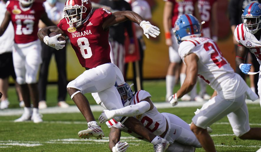 Indiana running back Stevie Scott III (8) slips a tackle by Mississippi linebacker Jacquez Jones during the first half of the Outback Bowl NCAA college football game Saturday, Jan. 2, 2021, in Tampa, Fla. (AP Photo/Chris O'Meara)