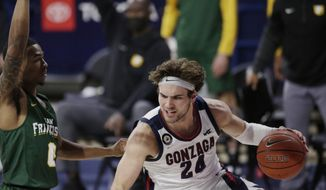 Gonzaga forward Corey Kispert, right, dribbles while pressured by San Francisco guard Khalil Shabazz during the first half of an NCAA college basketball game in Spokane, Wash., Saturday, Jan. 2, 2021. (AP Photo/Young Kwak)