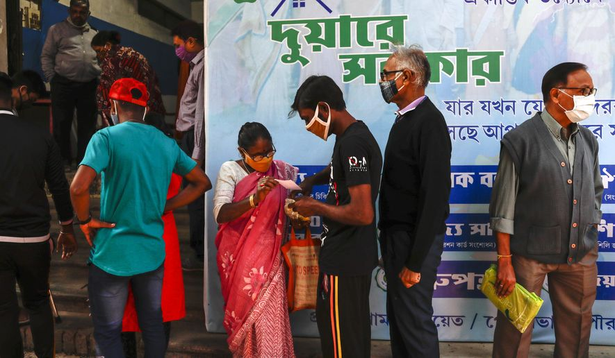 Indians wearing face masks as a precautionary measure against the coronavirus stand in a queue to apply for a health card initiated by West Bengal state government in Kolkata, India, Saturday, Jan. 2, 2021. (AP Photo/Bikas Das)