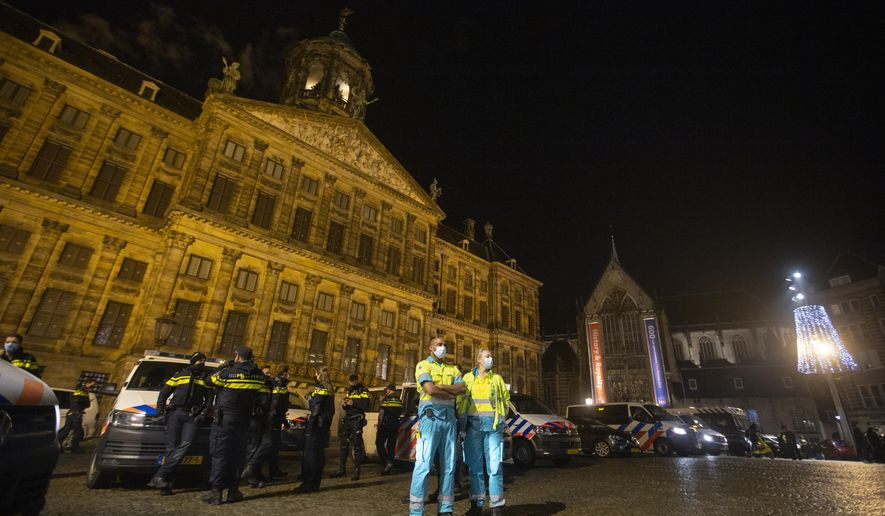 Police and ambulance personnel line up in front of the Royal Palace on Dam Square just before midnight in Amsterdam, Netherlands, Thursday, Dec. 31, 2020. As the world says goodbye to 2020, a year ruined by the coronavirus, there will be countdowns and live performances, but no massed jubilant crowds in traditional gathering spots like the Champs Elysees in Paris and New York City's Times Square this New Year's Eve. (AP Photo/Peter Dejong)