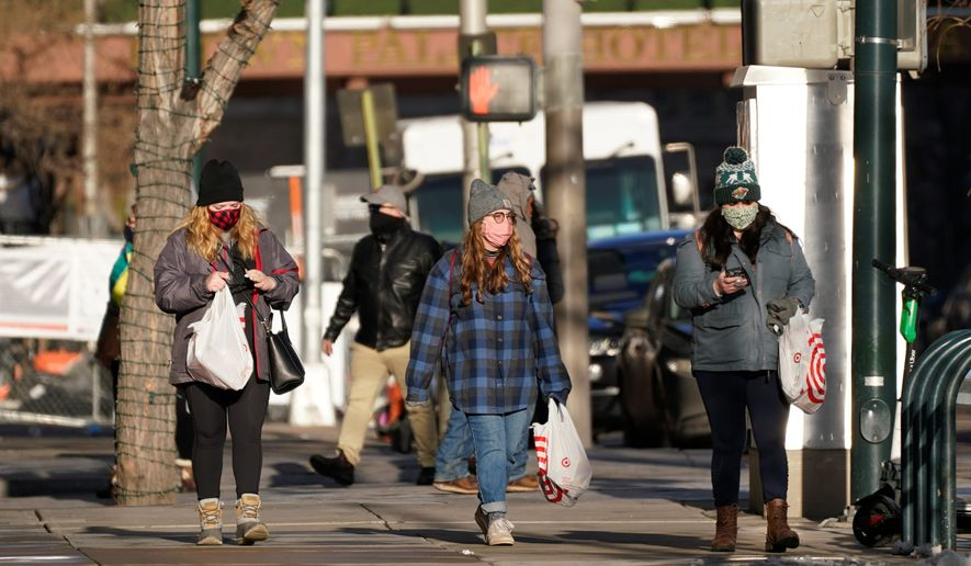 """""""Maybe the cough is the new smoking-in-public. If you're doing it without a face mask, you'll be looked at awkwardly,"""" said Dr. Panagis Galiatsatos, an assistant professor at Johns Hopkins School of Medicine. FILE - In this Tuesday, Dec. 29, 2020, file photo, shoppers wear face masks while in search of after-Christmas bargains in shops in the Denver Pavilions in downtown Denver. U.S. health officials say the lack of reported travel history for a Colorado National Guardsman with a new variant of the coronavirus suggests it is already spreading in the U.S. Dr. Greg Armstrong of the CDC says the agency is working with a national lab to broaden the search for the variant. (AP Photo/David Zalubowski, File) (Associated Press)"""