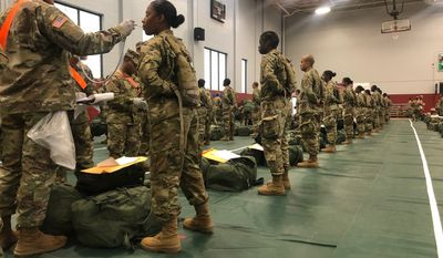 In this image provided by the U.S. Army, recent Army basic combat training graduates have their temperatures taken as they arrive at Fort Lee, Va, on March 31, 2020, after being transported using sterilized buses from Fort Jackson, S.C. (U.S. Army via AP)