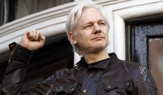 In this May 19, 2017, file photo, WikiLeaks founder Julian Assange greets supporters outside the Ecuadorian embassy in London, where he has been in self-imposed exile since 2012. (AP Photo/Frank Augstein, File)