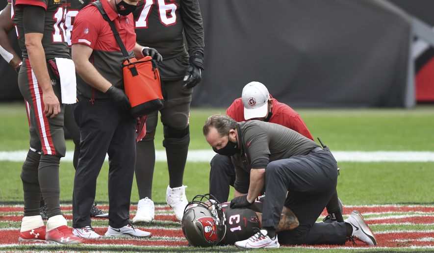 Tampa Bay Buccaneers quarterback Tom Brady (12) and offensive tackle Donovan Smith (76) look on as wide receiver Mike Evans (13) is looked after after getting injured against the Atlanta Falcons during the first half of an NFL football game Sunday, Jan. 3, 2021, in Tampa, Fla. (AP Photo/Jason Behnken)
