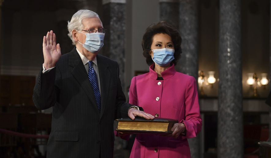 Sen. Mitch McConnell, R-Ky., participates in a mock swearing-in as his wife Transportation Secretary Elaine Chao holds a Bible, in the Old Senate Chamber at the Capitol in Washington, Sunday, Jan. 3, 2021. (Kevin Dietsch/Pool via AP)