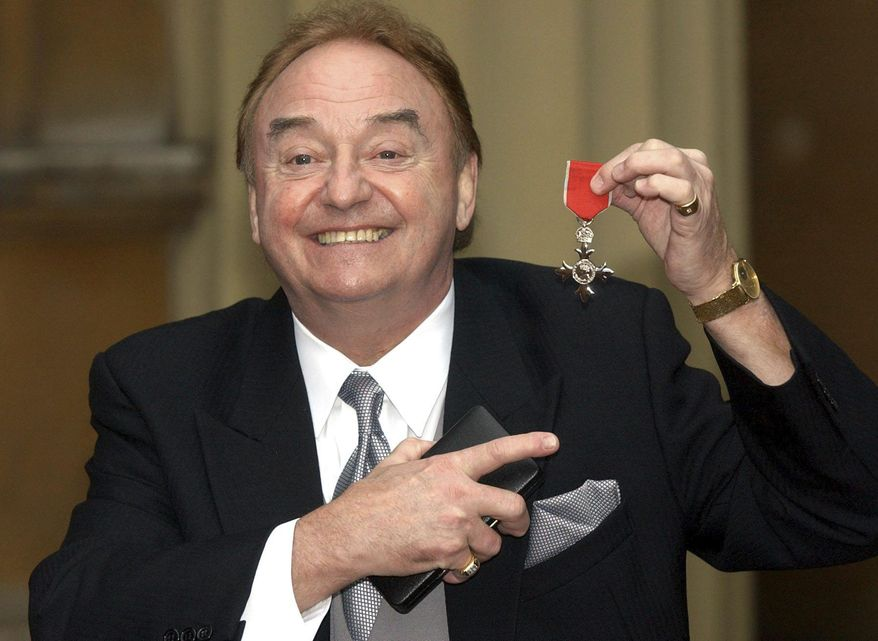 """FILE - In this Dec. 12, 2003 file photo, Gerry Marsden holds his MBE. Gerry Marsden, the British singer and lead singer of Gerry and the Pacemakers, who was instrumental in turning a song from the Rodgers and Hammerstein musical """"Carousel"""" into one of the great anthems in the world of football, has died. He was 78. (Matthew Fearn/PA via AP, File)"""