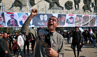 A man chants slogans against the United States while supporters of Popular Mobilization Forces hold posters of Abu Mahdi al-Muhandis, deputy commander of the Popular Mobilization Forces, and General Qassem Soleimani, head of Iran's Quds force during a protest, in Tahrir Square, Iraq, Sunday, Jan. 3, 2021. Thousands of Iraqis converged on a landmark central square in Baghdad on Sunday to commemorate the anniversary of the killing of Soleimanil and al-Muhandis in a U.S. drone strike. (AP Photo/Khalid Mohammed) **FILE**