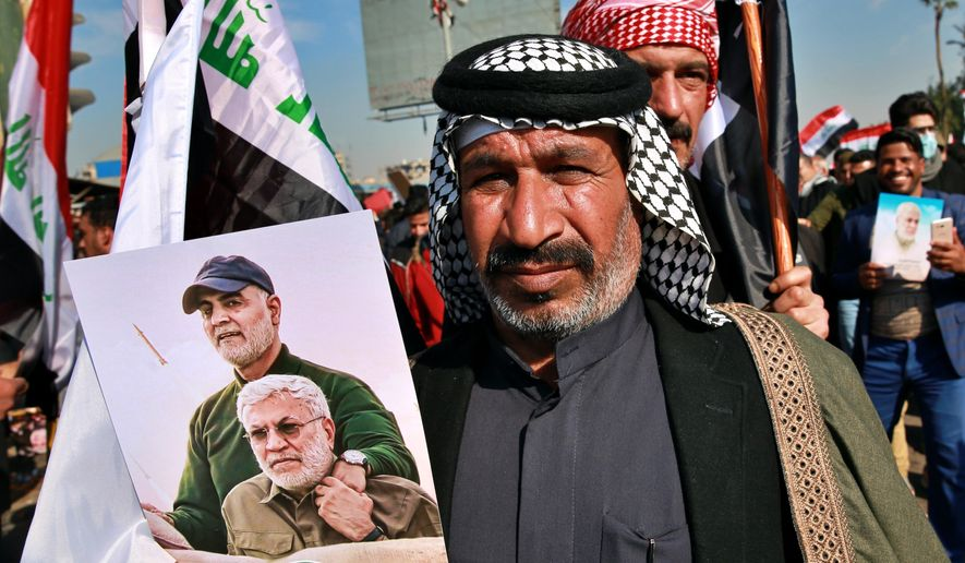 Supporters of the Popular Mobilization Forces hold posters of Abu Mahdi al-Muhandis, deputy commander of the Popular Mobilization Forces, front, and General Qassem Soleimani, head of Iran's Quds force during a protest, in Tahrir Square, Iraq, Sunday, Jan. 3, 2021. Thousands of Iraqis converged on a landmark central square in Baghdad on Sunday to commemorate the anniversary of the killing of Soleimanil and al-Muhandis in a U.S. drone strike. (AP Photo/Khalid Mohammed)