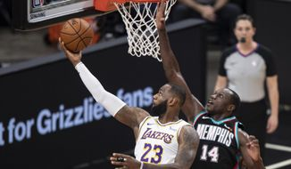 Los Angeles Lakers forward LeBron James (23) shoots past Memphis Grizzlies center Gorgui Dieng (14) during the first half of an NBA basketball game Sunday, Jan. 3, 2021, in Memphis, Tenn. (AP Photo/Wade Payne)