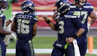 Seattle Seahawks wide receiver Tyler Lockett (16) celebrates his touchdown with quarterback Russell Wilson (3) during the second half of an NFL football game against the San Francisco 49ers, Sunday, Jan. 3, 2021, in Glendale, Ariz. (AP Photo/Ross D. Franklin)