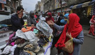 Indians, some of them, wearing face masks as a precautionary measure against the coronavirus shop at a Sunday market in Jammu, India, Sunday, Jan.3, 2021. India authorized two COVID-19 vaccines on Sunday, paving the way for a huge inoculation program to stem the coronavirus pandemic in the world's second most populous country. (AP Photo/Channi Anand)