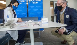 Louisiana Governor John Bel Edwards, right, talks with Dr. Mona Moghareh, a pharmacist with Ochsner Medical Center in Jefferson, La., as she sets up a station to administer the first vials of the coronavirus vaccine on Monday, Dec. 14, 2020. (Chris Granger/The Advocate via AP)