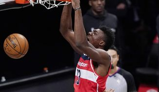 Washington Wizards center Thomas Bryant (13) dunks over Brooklyn Nets center Jarrett Allen (31) during the third quarter of an NBA basketball game, Sunday, Jan. 3, 2021, in New York. (AP Photo/Kathy Willens)
