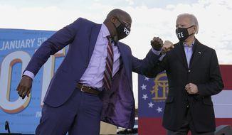 President-elect Joe Biden elbow bumps Senate candidate Raphael Warnock in Atlanta, Monday, Jan. 4, 2021, during a campaign rally for Warnock and Jon Ossoff. (AP Photo/Carolyn Kaster)