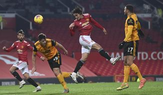 Manchester United's Edinson Cavani tries to score with a header during the English Premier League soccer match between Manchester Utd and Wolverhampton Wanderers at Old Trafford stadium in Manchester, England, Tuesday,Dec. 29, 2020. (Laurence Griffiths, Pool via AP)