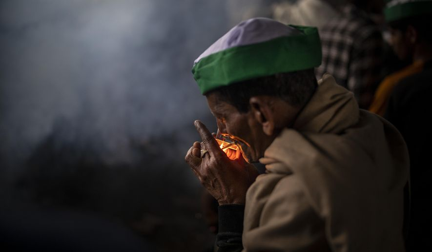 A farmer, sitting next to a bonfire, lights a bidi, or hand-rolled tobacco, as they block a major highway in a protest against new farm laws while it rains at the Delhi-Uttar Pradesh state border, India, Monday, Jan. 4, 2021. Ignoring the coronavirus pandemic, the farmers have been blockading highways connecting New Delhi to northern India for nearly five weeks, obstructing transportation and dealing a blow to manufacturing and businesses in the north. (AP Photo/Altaf Qadri)