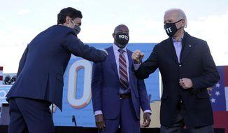 President-elect Joe Biden campaigns in Atlanta, Monday, Jan. 4, 2021, for Senate candidates Raphael Warnock, center, and Jon Ossoff, left. (AP Photo/Carolyn Kaster)