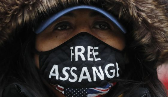 A Julian Assange supporter wears a face mask bearing his name outside the Old Bailey in London, Monday, Jan. 4, 2021. (AP Photo/Frank Augstein)