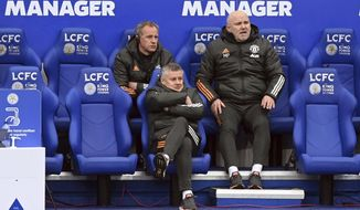 Manchester United manager Ole Gunnar Solskjaer, center, sits on the bench during the English Premier League soccer match between Leicester City and Manchester United at the King Power Stadium in Leicester, England, Saturday, Dec. 26, 2020. (Michael Regan/Pool via AP)