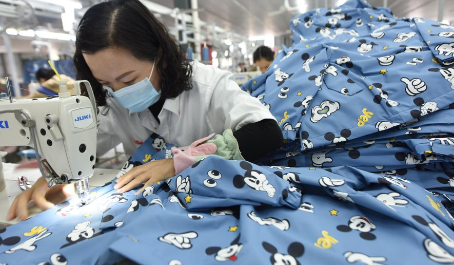 FILE - In this Oct. 27, 2020, file photo, a woman wearing a mask works in a garment factory in Donghai county in east China's Jiangsu province. China's manufacturing activity improved in December, 2020 but at its weakest rate in three months as the economy recovered from the coronavirus pandemic while its trading partners struggled with rising infections, according to two surveys. (Chinatopix Via AP)
