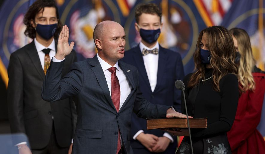 Utah Governor Spencer Cox takes his inaugural oath during an event at Tuacahn Center for the Arts in Ivins, Utah with his wife Abby at his side on Monday, Jan. 4, 2021. (Scott G Winterton/The Deseret News via AP)