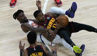 New York Knicks center Mitchell Robinson (23) battles Atlanta Hawks guard Brandon Goodwin (0) for the ball during the first half of an NBA basketball game Monday, Jan. 4, 2021, in Atlanta. (AP Photo/John Bazemore)