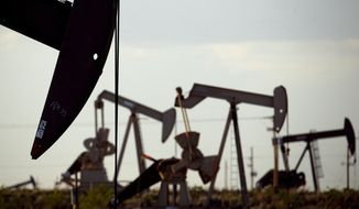 In this April 24, 2015, photo, pumpjacks work in a field near Lovington, N.M. Oil and gas development infused $2.8 billion into New Mexico coffers during the 2020 fiscal year and marked its second-highest total revenue ever reported despite a global price war and plummeting demand amid the coronavirus pandemic, according to a report released Monday, Dec. 21, 2020. (AP Photo/Charlie Riedel) **FILE**