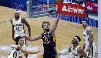 Indiana Pacers forward Domantas Sabonis (11) shoots between New Orleans Pelicans center Jaxson Hayes and guard Josh Hart (3) in the first half of an NBA basketball game in New Orleans, Monday, Jan. 4, 2021. (AP Photo/Gerald Herbert)
